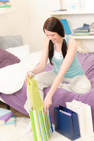 uitpakken: Young happy attractive girl unpack shopping bags in student appartment
