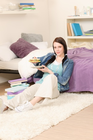 Young happy student have sandwich sitting in student apartment photo