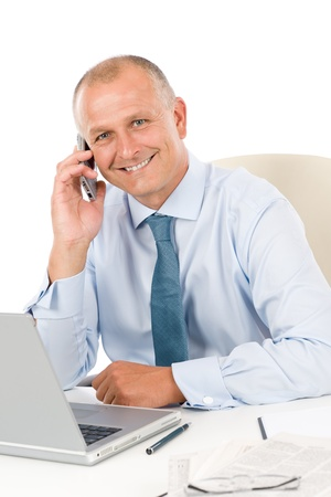 Portrait of successful smiling businessman sitting behind table photo