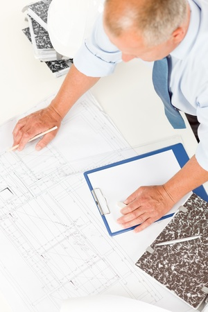 Closeup of senior man working on blueprints and construction plans photo