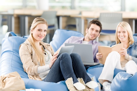 Group of young high-school students relaxing with books and laptop photo