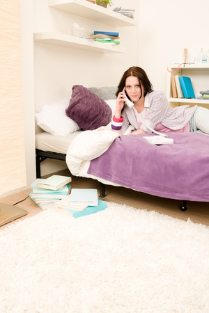Student apartment - young girl speaking on phone lying on bed Stock Photo - 9682511