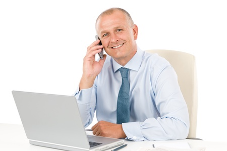teleworking: Portrait of successful smiling businessman sitting behind table