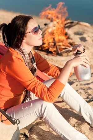 Camping happy woman sitting by campfire relaxing on beach photo