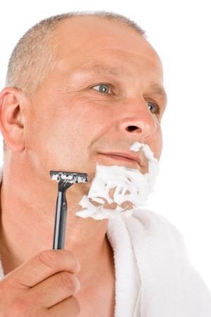 Portrait of mature handsome man shaving his beard photo