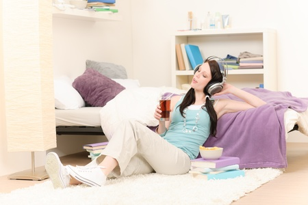 Young happy girl relax listen to music in student apartment photo
