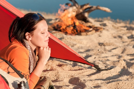 Camping happy woman relax lying in tent by  campfire photo