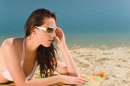 Summer beach stunning young woman sunbathing in bikini photo