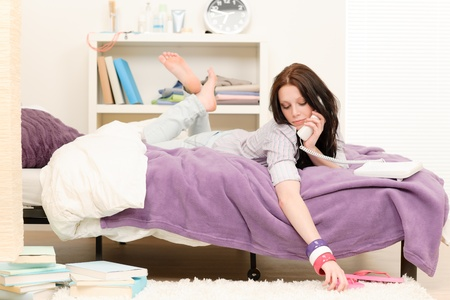 Student apartment - young girl speaking on phone lying on bed Stock Photo - 9754642