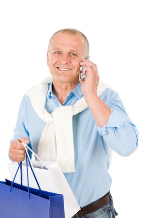 Elegant happy senior man holding shopping bags on phone photo