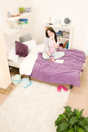 teen girl bedroom: Student apartment - young girl speaking on phone sitting on bed Stock Photo