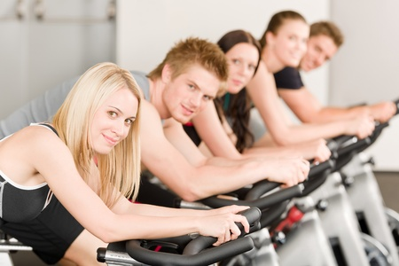 Fitness group of people on bicycle doing spinning at gym