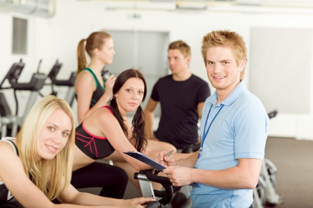 Young fitness instructor with gym people spinning or at cross-trainer photo