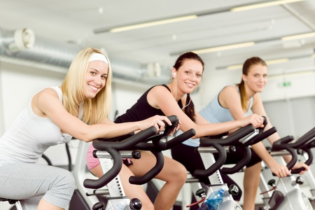 Fitness young woman on gym bike spinning indoor cardio exercise