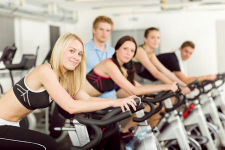 Young fitness people doing spinning with instructor at gym photo