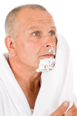 Portrait of mature handsome man wiping shaving foam with towel photo