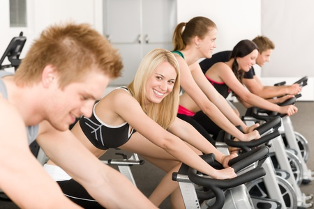 Fitness group of people on bicycle doing spinning at gym photo