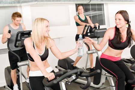 Fitness young girl on gym bike - crosstrainer in background photo
