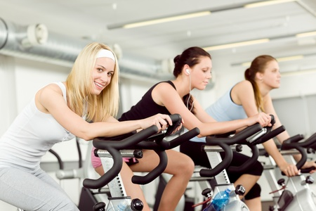 Fitness young woman on gym bike spinning indoor cardio exercise photo