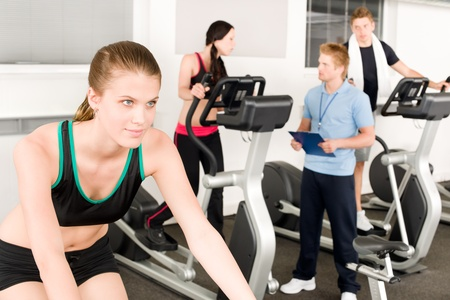 fitness instructor: Young fitness woman doing spinning on bicycle with gym instructor