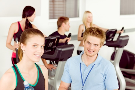 cardio exercise: Young fitness instructor with gym people cardio exercise at cross-trainer Foto de archivo