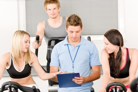 Young fitness instructor with gym people spinning or at cross-trainer Stock Photo