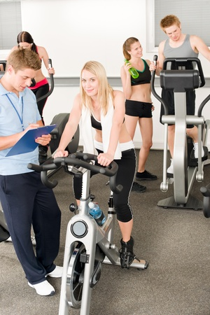 Fitness young girls at gym bicycle with instructor doing spinning photo