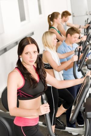 eliptica: Grupo de j�venes de gimnasio en el entrenador de Cruz el�ptica en el gimnasio de la salud