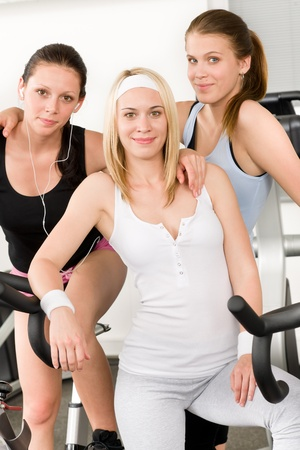 Fitness young girls on gym bike indoor cardio exercise posing photo