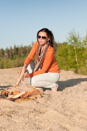 Camping happy woman make campfire on beach blue sky photo
