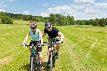 Sport mountain biking - man pushing young girl uphill sunny countryside photo
