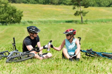 Sport mountain biking couple relax in meadows sitting drink water photo