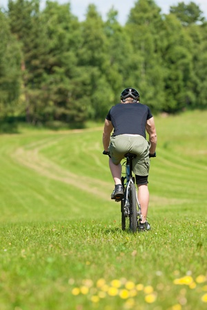 coutryside: Fit young man cycling downhill mountain bike in summer coutryside Stock Photo