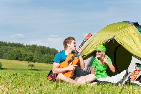 Happy camping couple sitting by tent play guitar sunny countryside Stock Photo - 9825065