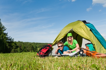 Happy camping couple lying inside tent backpack in sunny countryside photo