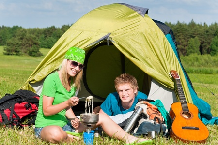 Young camping couple cooking meal outside tent in sunny countryside Stock Photo - 9824439