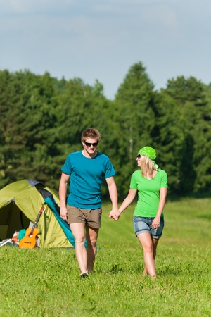 Young camping couple hold hands in summer countryside tent photo