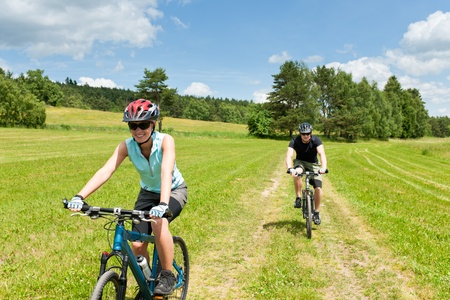 Sport couple riding mountain bicycles in coutryside meadows photo