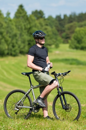 Fit young cycling man relax with water bottle in summer coutryside photo