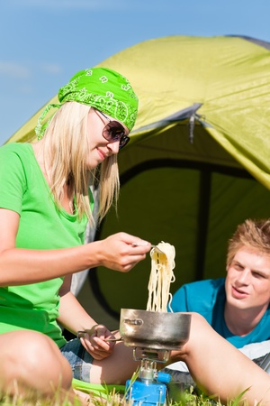 Young camping couple cooking meal outside tent in sunny countryside photo