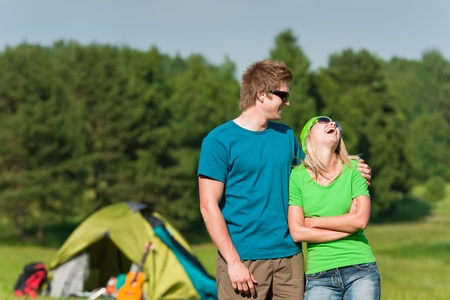 Young camping couple hugging in summer countryside tent in background photo