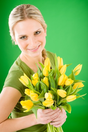 Young blond happy woman hold yellow tulips flower on green photo