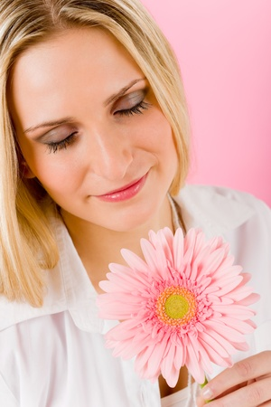Young happy woman hold pink gerbera daisy looking at blossom photo