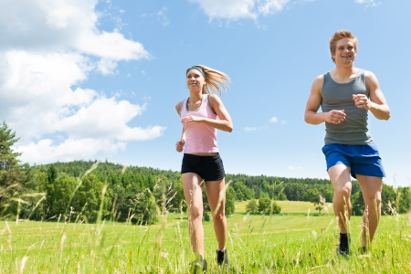 Young fit couple jogging on summer day in meadows countryside photo