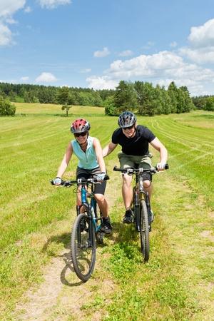 hombre empujando: Deporte ciclismo de monta�a - hombre empujar campo soleado cuesta arriba de ni�a Foto de archivo