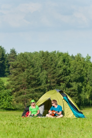 Young camping couple cooking meal play guitar in sunny countryside Stock Photo - 9981779