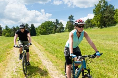 andando en bicicleta: Pareja feliz deporte montando bicicleta en coutryside meadows Foto de archivo