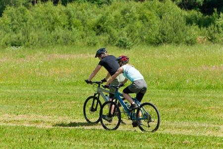 Sport mountain biking happy couple riding downhill in sunny countryside photo