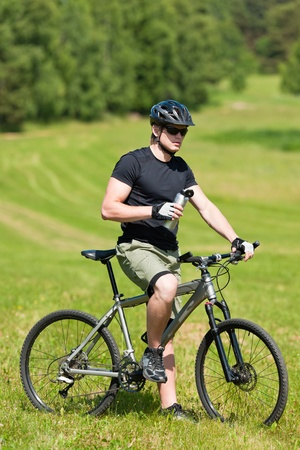 coutryside: Fit young cycling man relax with water bottle in summer coutryside