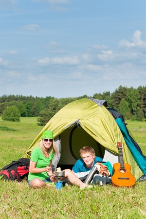 Young camping couple cooking meal outside tent in sunny countryside Stock Photo - 9981870